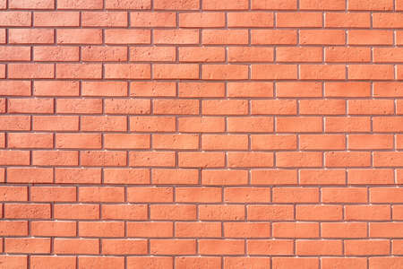 Wall with decorative finish imitation of red brick, background.
