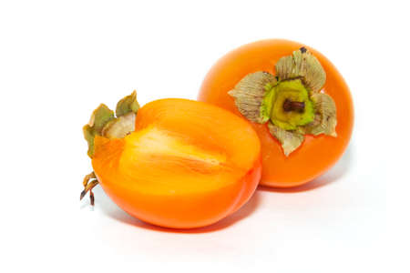 ferm: two persimmons, one sliced, close-up on a white background