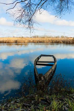 sunken boat: late autumn landscape with half-sunken boat on the river