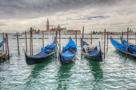 Venetian gondolas on water in cloudy weather HDR photo