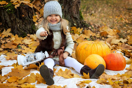 girl sitting on a blanket with pumpkins and a lantern on a background of yellow autumn leaves photo
