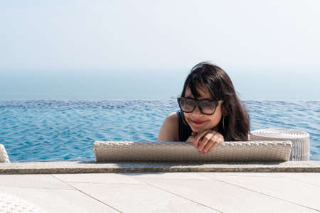 Smiling  asian woman sitting backward on a wicker daybed near swimming pool Stock Photo