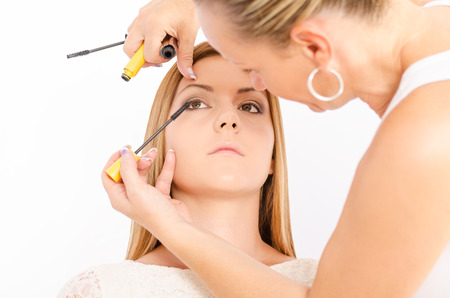Make up artist applying a mascara on a young and beautiful female model photo