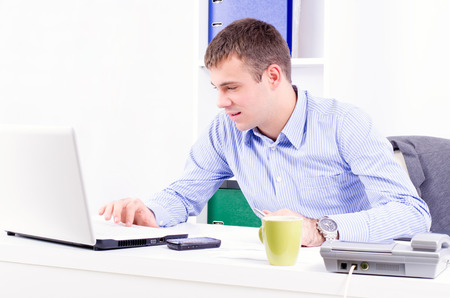 young adult man: Young and handsome businessman in his office working and looking at the laptop