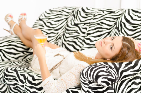 Beautiful young woman lying and relaxing on a sofa holding a glass of wine and looking at the camera with her legs crossed photo