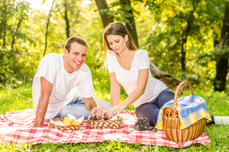 Happy young couple having a picnic eating grapes and sitting on the picnic cloth enjoying the autumn nature in the park photo