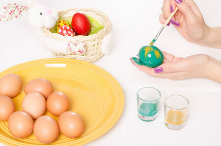 Colouring Easter eggs with green and yellow colour brush and serviette on a white table photo