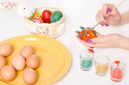Colouring Easter eggs with red yellow and green colour brush and serviette on a white table photo