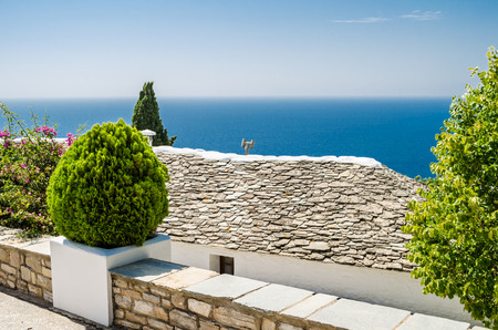 next horizon: Beautiful panoramic sea view from the hill next to traditional Greek stone house with the horizon  in a distance in Thassos Greece Stock Photo