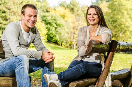 Happy young couple sitting on a bench and enjoying the autumn nature in the park photo