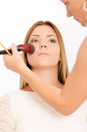 Make up artist applying make up on a young and beautiful female model photo
