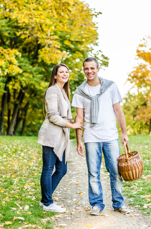 Happy young couple standing on a path and enjoying the autumn nature in the park photo