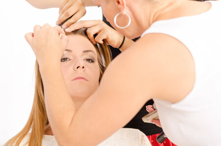 Make up artist applying make up and a hairdresser preparing the hair on a young and beautiful female model photo