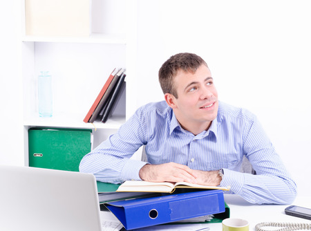 Young handsome businessman in his office working thinking and looking a side photo
