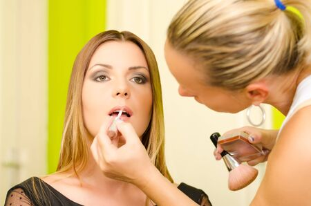 Make up artist applying lipstick on a young and beautiful female model  photo