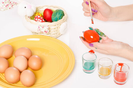 Colouring Easter eggs with orange colour brush and serviette on a white table photo