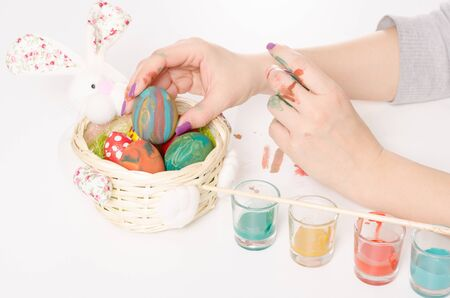Filling and decorating bunny basket with coloured eggs on a white table photo