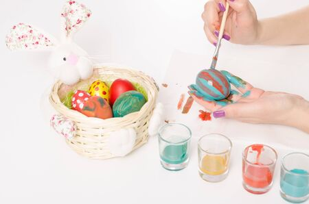 Colouring Easter eggs with blue and red colour brush and serviette on a white table photo