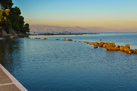 mainland: Sunset at Kanoni beach in Corfu Town at Corfu Island Greece with Greek mainland mountains in the background