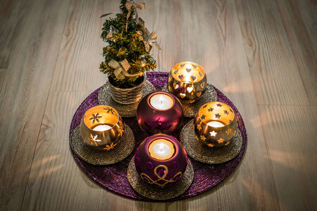 candleholders: Purple and silver christmas candleholders and a small christmas tree on a purple decoration pad with a wooden pattern background