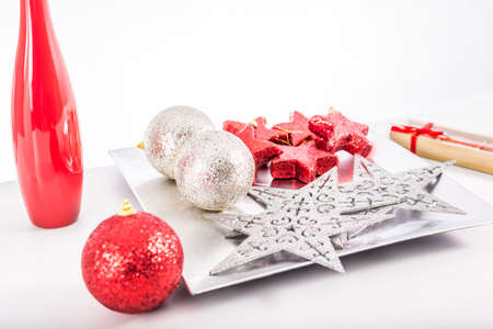Red and silver christmas balls and stars on a silver decoration tray with a red and white decoration vases on a white background photo