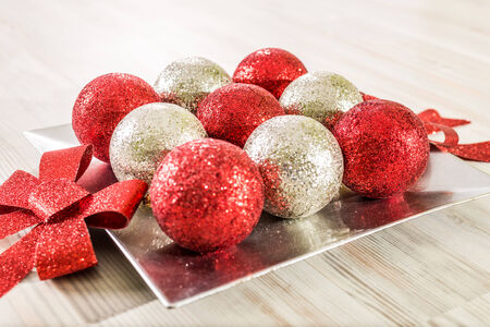 Red and silver christmas balls on a silver decoration tray with a wooden pattern background photo