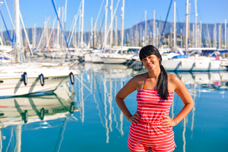 Beautiful young girl standing in front of the sailing boats and posing in the harbour photo