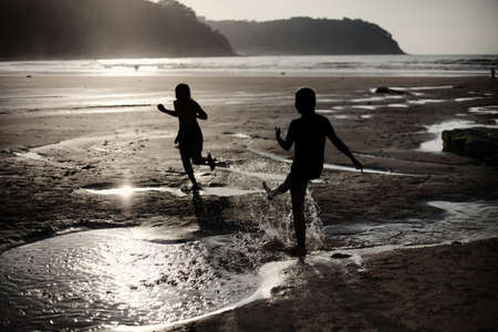 Children on the beach playing with water  Backlighting