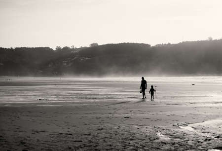 Mother and son on the beach walking and looking for shells. Sunset in backlight. photo