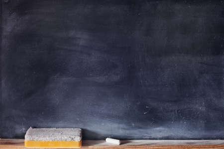 Blank blackboard with white chalk and eraser