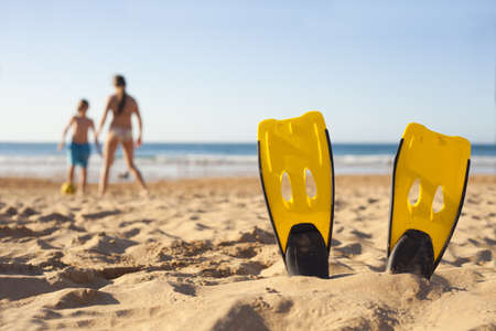 Children playing on the beach behind diver fins