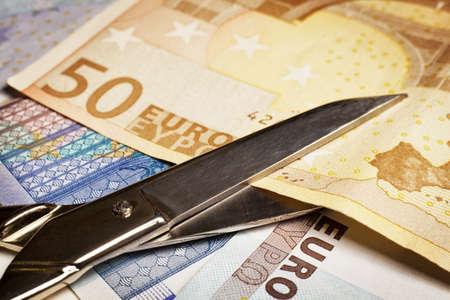cutting costs: Cutting Costs Idea. Scissors cut a 50 euros Paper Currency.