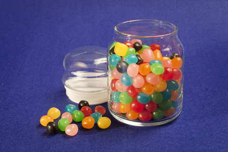 jellybean: Open jar of multi colored Jelly Beans. Blue background. Stock Photo