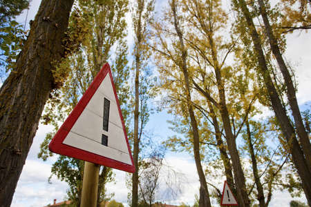 Warning Sign on road by autumn forest Stock Photo - 16354425