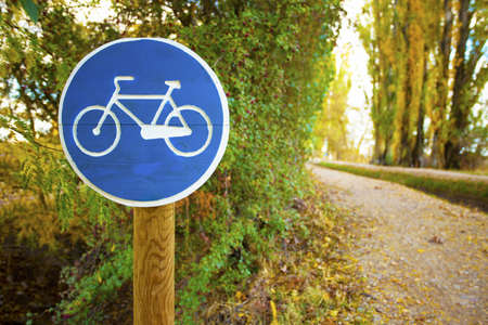 Wooden Post of Bicycle sign on a park. Valladolid, Spain.