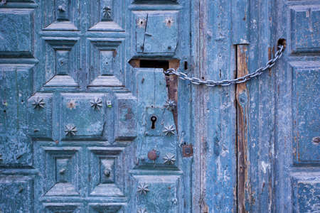 Old blue wooden door closed by a chain. Macro shot. photo