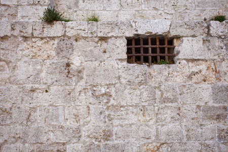 Window of an ancient dungeon with stone wall Stock Photo