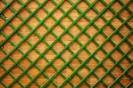 Brick wall with green wooden trellis.