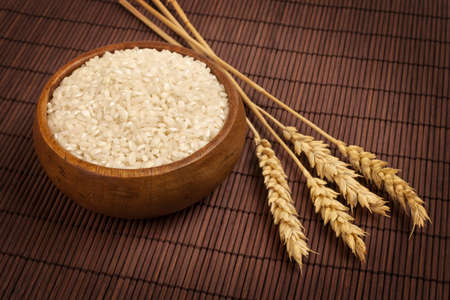 Wooden bowl of raw rice with wheat spikes