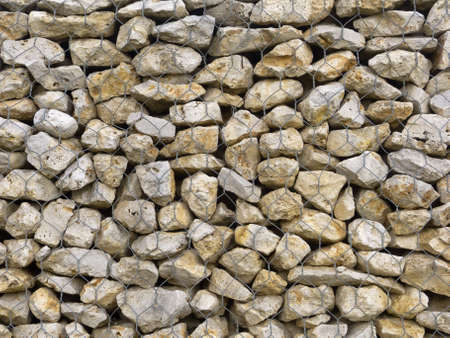 meshed: Retaining wall made of meshed boxes of stones. Macro shot for backgrounds
