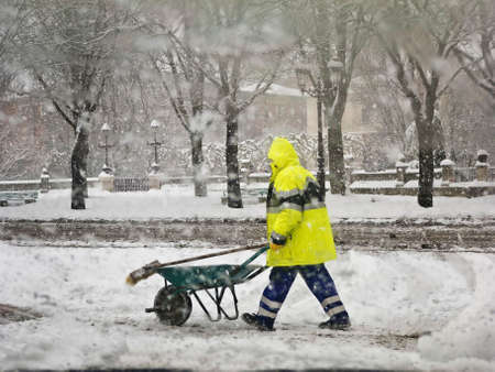 Worker in uniform removing snow in winter snowstorm.