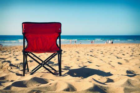 strandstoel: Rode stoel op het strand met vage mensen op de achtergrond. Cross procesing effecten. Stockfoto