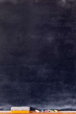 Blank blackboard with colored chalks and eraser. Vertical composition. Standard-Bild