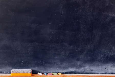 espalda: Blanco de la pizarra con tizas de colores y goma de borrar. Composici�n horizontal. Foto de archivo