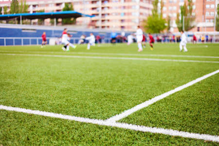 Limit lines of a sports grass field with defocused football players