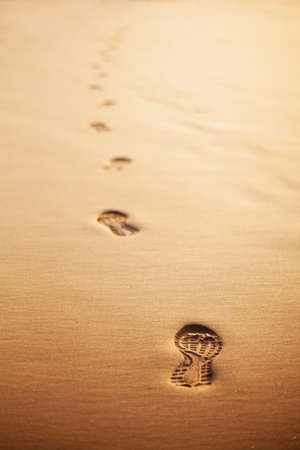 Trail of human footprints on the beach at sunset. Selective focus. Stock Photo