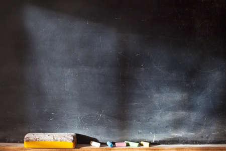 着色されたチョーク、消しゴムと光の効果を持つ空白の黒板。水平方向の組成物。