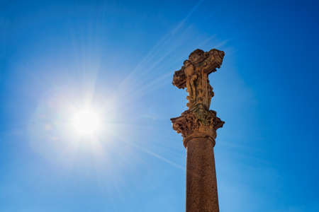 Old stone crucifix with sun rays in backlit
