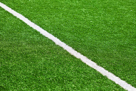Limit line of a sports grass field for Background. White line. Selective Focus.