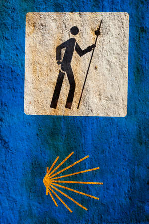 Sign of the Camino de Santiago over stone. Pilgrimage route to the Cathedral of Santiago de Compostela, Spain.